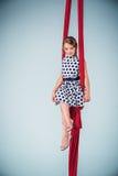 Behagfullt gymnastsammanträde med röda tyger royaltyfri foto