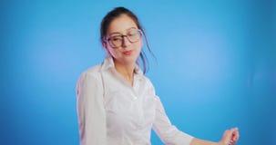 Behagit le ung flickadansen som isoleras på blå bakgrund Student glädje, uttryck arkivfilmer