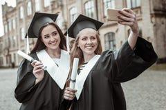 Behagit två kvinnlig som tillsammans gör selfiefotoet royaltyfri foto