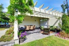Behandeld terrasgebied met buitenstoelen in de binnenplaatstuin Mening van de portiek van de ingangskolom met treden en gang stock afbeelding