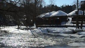Behandelde het plattelandshuisje van de zomerhuizen winter van de sneeuw de snelle bevroren rivier stock footage