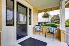 Behandelde portiek met zwarte voordeur en twee rieten stoelen Royalty-vrije Stock Afbeeldingen