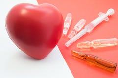 Behandeling, steun met medicijn en hartbescherming Drugs - flesjes en spuit op rode die achtergrond op hart wordt gericht, dat Ne stock foto