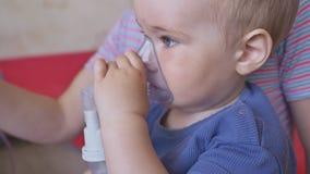 Behandeling van longziekte met een inhaleertoestel Een kleine jongen in het masker van een inhaleertoestel Behandeling thuis stock video