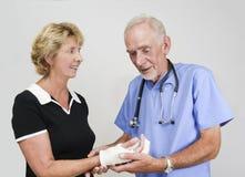 Behandeln Sie überprüfende ältere Frau mit der Hand in der Form lizenzfreies stockfoto