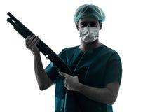 Behandeln Sie Chirurgmann mit der Gesichtsmaske, die Schrotflintenschattenbild hält Stockbilder