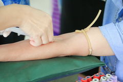 Behandeln Sie Düsennadelspritze auf Arm, um Blut für Test zu sammeln die Gesundheit Lizenzfreie Stockfotos