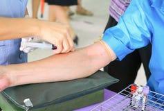 Behandeln Sie Düsennadelspritze auf Arm, um Blut für Test zu sammeln die Gesundheit Stockbilder