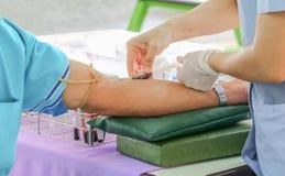 Behandeln Sie Düsennadelspritze auf Arm, um Blut für Test zu sammeln die Gesundheit Stockfotos