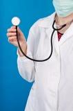 Behandeln Sie das Anhalten eines Stethoskops auf einem blauen Hintergrund Lizenzfreies Stockfoto