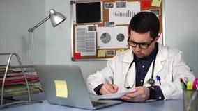 Behandeln Sie das Arbeiten am Arbeitsplatz mit Notizbuch und medizinischen Formen stock footage