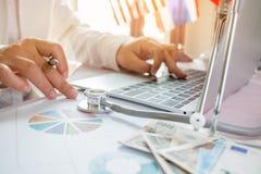 Behandeln Sie das Arbeiten an Laptop-Computer mit Berichtsanalyse und -geld stockbild