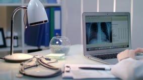 Behandeln Sie das Arbeiten mit Röntgenstrahl auf Laptop am Arbeitsplatz Radiologekontrollröntgenstrahlbild stock video