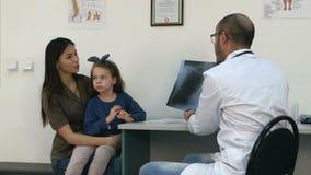 Behandeln Sie das Erklären des Brustradiographiebildes der Mutter, die kleine Tochter in ihren Armen hält stock video