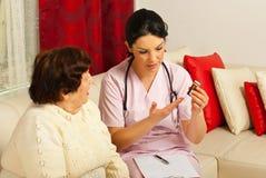 Behandeln Sie das Geben der älteren Frau von Medizin Stockbild