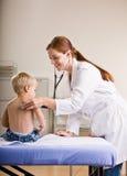 Behandeln Sie das Geben von Jungenüberprüfung im Doktorbüro Lizenzfreie Stockfotos