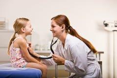 Behandeln Sie das Geben von Mädchenüberprüfung im Doktorbüro Lizenzfreies Stockfoto