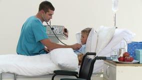 Behandeln Sie das Hören auf einen childs Kasten mit Stethoskop stock footage