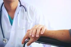 Behandeln Sie das Halten älterer geduldiger ` s Hand in einem wheelchai und SU geben stockfoto