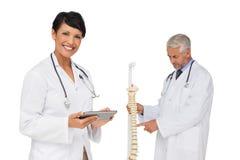 Behandeln Sie das Halten der digitalen Tabelle mit Kollegen durch skeleton Modell Lizenzfreies Stockbild