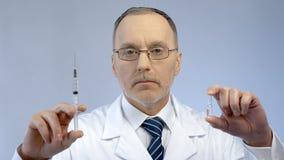 Behandeln Sie das Halten der Spritze und der Ampulle und effektive Medikation zum Patienten vorschreiben lizenzfreies stockbild