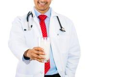 Behandeln Sie das Halten des Glases Milch vor Kasten, gut für Osteoporose- und Knochengesundheit lizenzfreies stockbild