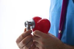 Behandeln Sie das Halten eines Herzens und des Stethoskops auf weißem Hintergrund Lizenzfreie Stockfotos