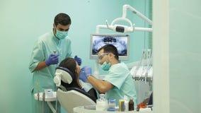 Behandeln Sie das Handeln der zahnmedizinischen Behandlung zu seinem Patienten in der Klinik stock video footage