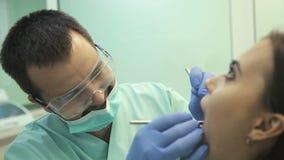 Behandeln Sie das Handeln der zahnmedizinischen Behandlung zu seinem Patienten in der Klinik stock footage