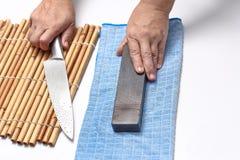 Behandeln Sie das Messer, um ein scharfes Messer mit einem Schleifstein herzustellen Lizenzfreie Stockfotos