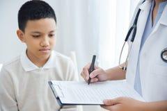 Behandeln Sie das Nehmen der Kenntnis über Checkliste für Patienten eines kleinen Jungen Stockfotografie