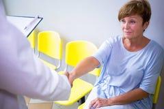 Behandeln Sie das Rütteln der Hand mit Patienten im Warteraum stockfotografie