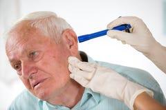 Behandeln Sie das Schauen in das Ohr des Patienten lizenzfreies stockfoto