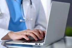 Behandeln Sie das Schreiben auf Laptop-Computer beim Sitzen am Glasschreibtisch im Krankenhausbüro Arzt bei der Arbeit Medizin un lizenzfreie stockbilder