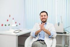 Behandeln Sie das Sitzen entspannt in seinem Stuhl im Büro und das Lächeln Lizenzfreies Stockbild