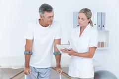 Behandeln Sie das Zeigen des Klemmbrettes zu ihrem Patienten mit Krücke lizenzfreie stockfotos