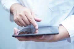 Behandeln Sie den Gebrauch, der in seiner Handdigitalen Tablette hält und E-Mail bei der Stellung in Pflegekrankenhaus liest stockfotografie