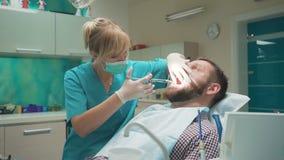 Behandeln Sie den Zahnarzt, der eine Einspritzung vom lokalen Betäubungsmittel in das Zahnfleisch macht stock footage