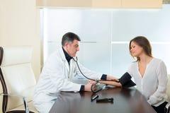 Behandeln Sie den Mann, der Blutdruckstulpe auf Frauenpatienten überprüft Stockfotos