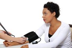 Behandeln Sie die Prüfung des Blutdruckes der schwangeren Frau. stockfotografie