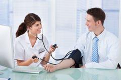 Behandeln Sie die Prüfung des Blutdruckes des Geschäftsmannes in der Klinik Lizenzfreies Stockfoto