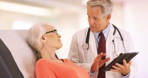 Behandeln Sie die Unterhaltung mit älterem Frauenpatienten im Büro stockbild