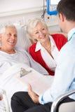 Behandeln Sie die Unterhaltung mit älteren Paaren im BRITISCHEN Krankenhaus Stockfoto