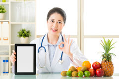 Behandeln Sie Ernährungswissenschaftler mit den Früchten, die digitale Tablette und okaysi halten Stockbilder