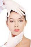 Behandeln Sie Hände in den Handschuhen, die das Schönheitsgesicht berühren. stockfoto