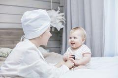 Behandeln Sie Herausforderungen und Festlichkeiten ein kleines Kind in einem Raum Stockfoto