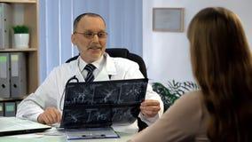 Behandeln Sie informierenden weiblichen Patienten über gute Ergebnisse des Schiffröntgenstrahls, Wiederaufnahme stockbild