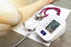Behandeln Sie messenden Blutdruck des Patienten, Digital-Blutdruck-Monitor auf hölzernem Hintergrund Stockfotos
