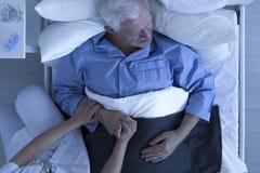 Behandeln Sie oder pflegen Sie das Halten der Hand des älteren Patienten lizenzfreie stockbilder