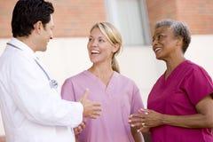 Behandeln Sie und die Krankenschwestern, die außerhalb eines Krankenhauses stehen Lizenzfreies Stockfoto
